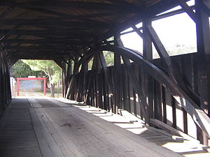 Cogan House Covered Bridge - Interior view of a Burr Arch and timber framing; the red metal framework beyond the west entrance prevents vehicles larger than the posted limits from entering.
