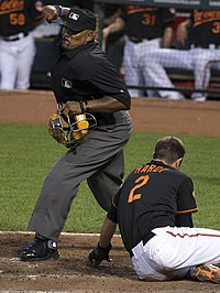 Home plate umpire Laz Díaz calls a runner out at home plate.