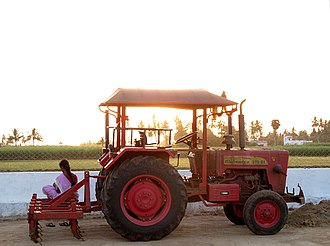 Mahindra 575 Di at sunset over a sugar cane field, Tamil Nadu, India Mahindra 575 Di -Tamil girl watching sunset at a village sugar cane field and palm trees sitting barefoot in pink Sari on a red tractor - Tamil Nadu village gas station with her mobile phone - myindiaexperience -feature story photo.jpg