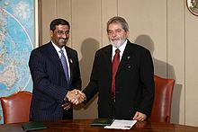 Two smiling men in business suits, shaking hands