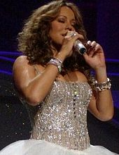 A woman smiles and holds a microphone, wearing a metallic dress.