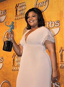 "An African American female with dark brown hair that reaches her shoulders. She is wearing a short sleeved light pink dress and a ring on her left hand. She is holding a greenish-blue statue that has a bronze plank with her right hand. In the background, there is an orange wall with logos and writing, such as the words ""tbs"" and ""TNT"" (which has a circle around it)."