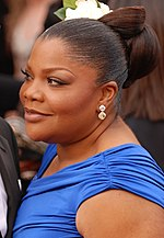 An African American female with dark brown hair up in a bun with a flower. She is wearing a short sleeved royal blue dress.