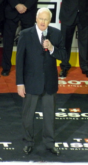 Costello in a suit and tie speaking into a microphone at an on-ice presentation
