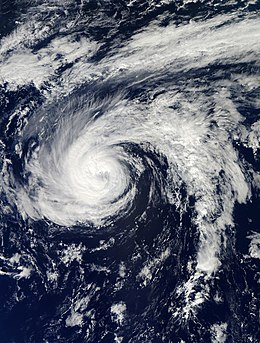 Satellite image of Hurricane Nadine. Toward the center, a small, faint eye is visible. A long spiral band also extends to the east.