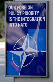 "A blue poster at a bus stop with the NATO logo and the words ""OUR FOREIGN POLICY PRIORITY IS THE INTEGRATION INTO NATO"" in white."