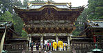 A two-storied, decorated wooden gate where the upper story extends over the lower. There is a bulging gable at the center under which a board with characters is attached.