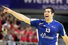 Nikola Karabatic, le bras droit tendu pour pour indiquer une direction.
