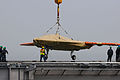 Personnel load a U.S. Navy X-47B Unmanned Combat Air System demonstrator aircraft onto the flight deck of the aircraft carrier USS George H.W. Bush (CVN 77) in Norfolk, Va., May 6, 2013 130506-N-CZ979-052.jpg