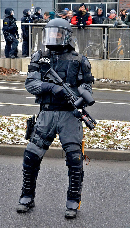 Heavily protected policeman of a German SEK in riot gear with Tac700 Pepperball Launcher. Polizist Pepperball Dresden.jpg