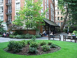 Circle of green grass about 10 yards in diameter, with a roughly 3 yard brown central area containing low bushes. Outward-facing park benches are at the circle's rim, and a multistorey brick building with an awning is in the background, across a sidewalk.