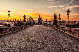 Un pont piétonnier, vide, au soleil couchant, avec des statues et des lampadaires tout du long; des bâtiments anciens à l'arrière plan.