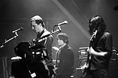 Black-and-white photograph of Queens of the Stone Age performing live in 2007.
