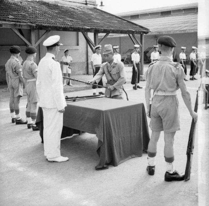 A Japanese officer surrenders his sword to a British Lieutenant in a ceremony in Saigon, French Indochina.