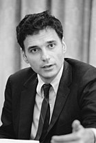 Young-looking Nader at 40+ years old gesturing as he speaks, wearing a coat and tie with unruly wavy dark hair.