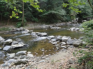 Stream restoration - Boulder step pools installed in Rock Creek, Washington, D.C. The pools raise the water level and allow fish to swim over a partially-submerged sewer pipe which crosses the creek.