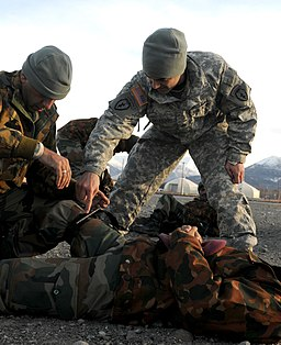 Sgt. Dakota Oklesso helps an Indian Army soldier apply a tourniquet