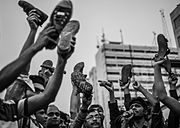 Protesters holding up shoes