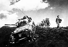 A tank of World War II vintage, with some foot soldiers marching alongside