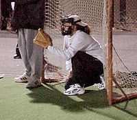A softball catcher wearing a mask for protection.
