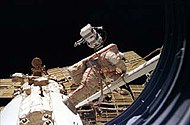 A man dressed in a white spacesuit with a red stripe manoeuvres along a boom-like crane towards a white cone-shaped space station module. Four arrays, one of which is damaged, project from the module, and the blackness of space forms the background. The rim of the porthole through which the photograph was taken is visible to the right of the image.