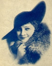 "Blue and white picture of a smiling dark-haired woman, facing the camera and looking to the right. She wears a dark brimmed hat and a fur coat. Her right hand is holding the fur coat and there's a ring in her little finger. The text ""Sophie Tucker"" is written on the picture with small white letters."