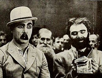 Jimmy Aubrey - Still from Squabs and Squabbles (1919), where Aubrey (at left) has painted eyes upon his eyelids so he can sleep during a meeting at a mission, but peeks when a man takes out his money