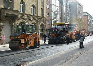 Foto einer städtischen Straßenbaustelle mit Asphaltfertiger und Kombiwalze