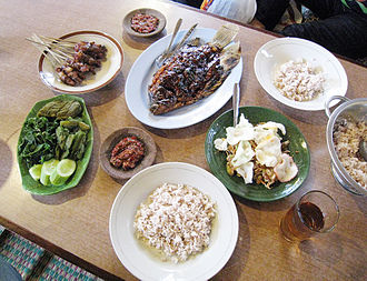 Sundanese cuisine - An example of Sundanese dishes in lesehan (seated on mat) style, which includes mutton satay, gurame bakar, karedok, rice, lalab and sambal.