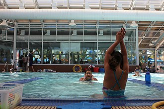 Swimming lessons - A five-year-old girl learns arm placement from her teacher in an individual class at a dedicated swimming school in San Jose, California. Other children learn in small group classes (far left and right).