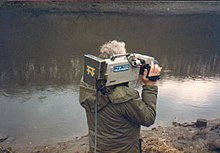 A man standing beside a river holding a camera with the Tyne Tees logo.