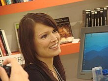 A smiling Turunen is seen in front of a book shelf and a computer screen.