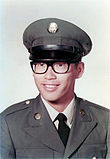 Asian American male wearing Army Dress Green Uniform and glasses posing for a photo.