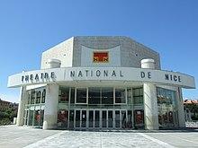 Vue d'une structure moderne ronde avec «Théâtre national de Nice» inscrit et dessus un toit plat octogonal.