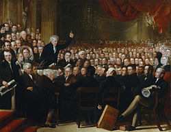 Oil painting of an impressive-looking Victorian man in his fifties enthusiastically addresses a packed hall of men and women.