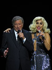 Bennett in suit on the left and Gaga in a sparkling dress and blonde hair singing onstage