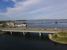 The bridge is in the foreground, with Casco Bay behind it. The Back Bay Footpath is underneath the bridge on the right, and some islands are in the background.