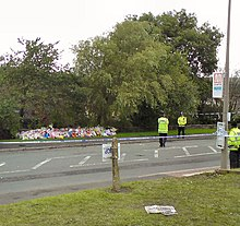 Three policeman stand near a large number of bouquets beside a road