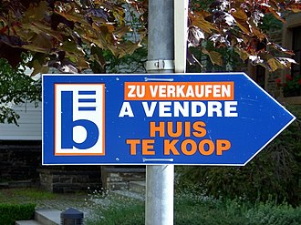 """Bilingual sign - Trilingual sign in Burg-Reuland, German-speaking Belgium in German, French and Dutch reading """"house for sale"""""""