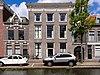 Patriciershuis achter gevel onder lijst met gesneden Lodewijk XIV-consoles. Geprofileerde hardstenen vensterdorpels