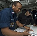 U.S. Navy Quartermaster 2nd Class Dante Coleman, foreground, conducts a maintenance and material management spot check for Ensign Matthew Hebert aboard the guided missile destroyer USS Gravely (DDG 107) 130425-N-KA046-094.jpg