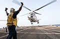 U.S. Navy Seaman Joseluis Robles directs an AS332 Super Puma helicopter to take off from the flight deck of the guided missile destroyer USS Winston S. Churchill (DDG 81) during a vertical replenishment at sea 120809-N-YF306-348.jpg
