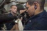 U.S. Navy Sonar Technician (Surface) 2nd Class Charles Granger, right, and Sonar Technician (Surface) 1st Class Christof Bessler inspect the locking bolt screws on a multi-functional towed array (MFTA) module 140103-N-PW661-017.jpg