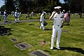 US Navy 050527-N-6477M-218 Naval Station Everett Chaplain, Lt. Cmdr. John M. Hakanson renders a salute after placing an American flag at the headstone of a veteran at the Grand Army of the Republic Cemetery in Snohomish, Wash.jpg