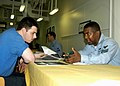 US Navy 050616-N-7869M-003 Aviation Boatswain's Mate Airman Keith Suiter, left, speaks to Boatswain's Mate 1st Class Jonathan Hall about enlisted service records at the Mentorship Information Fair.jpg