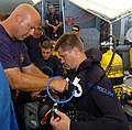US Navy 050624-N-8861F-001 U.S. Navy Diver Chief Electrician's Mate Mike Welsh helps Russian Navy Diver Igor Zhiazhivov check his gear before the dive aboard the salvage ship USS Grasp (ARS 51).jpg