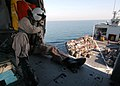 US Navy 051212-N-7945K-168 Aviation Electronics Technician 3rd Class Sean Lawrence, tells the pilot where to position their MH-60S Seahawk helicopter to pick up supplies from the Military Sealift Command (MSC) combat stores shi.jpg