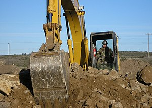 Digging - Construction equipment being used to dig up rocky ground.