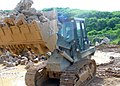 US Navy 070828-N-3713P-001 Equipment Operator Constructionman Apprentice Chance R. Keiter, attached to Naval Mobile Construction Battalion (NMCB) 4, uses a front end loader to load a dump truck with rock from a recent blast at.jpg