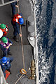 US Navy 081020-N-1635S-005 Sailors retrieve line aboard the Ticonderoga-class guided-missile cruiser USS Chancellorsville (CG 62) while conducting a replenishment at sea with the Military Sealift Command fast combat support shi.jpg